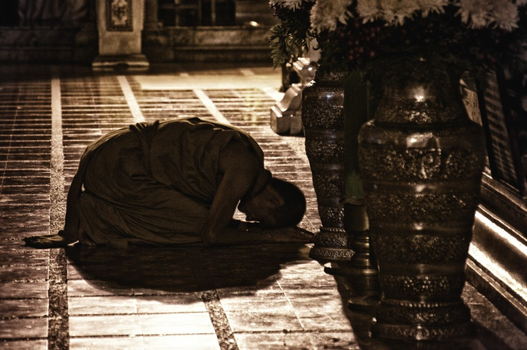 monk bowing to buddha